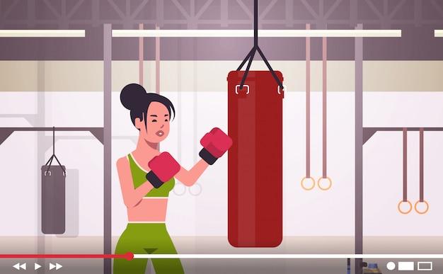 Blogger donna colpire enorme sacco da boxe sportswoman boxer vlogger registrazione video online Vettore Premium