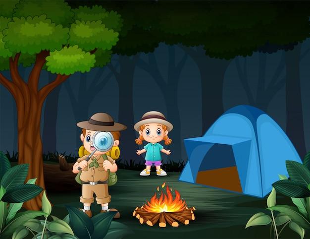Boy explorer con lente di ingrandimento con una ragazza nella foresta Vettore Premium