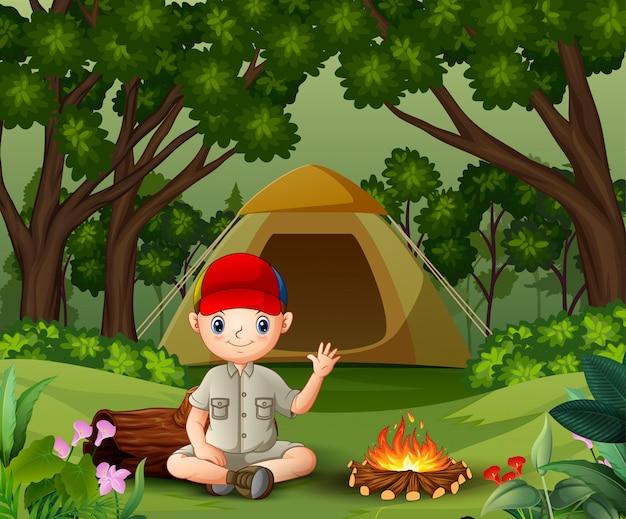 Boy scout seduto vicino al fuoco Vettore Premium
