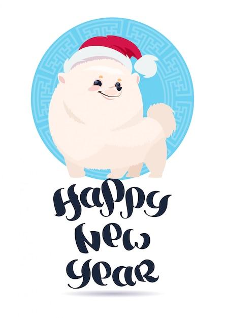 Cane bianco di pomerian in santa hat sulla progettazione di iscrizione di festa della cartolina d'auguri del buon anno Vettore Premium