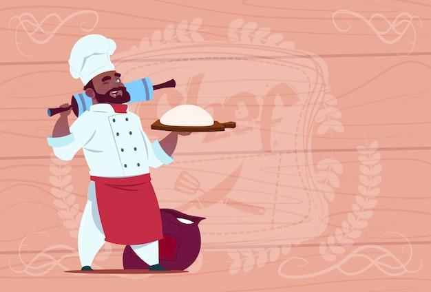Capo sorridente del cuoco unico afroamericano della tenuta del cuoco e della farina del cuoco unico in uniforme bianca del ristorante sopra fondo strutturato di legno Vettore Premium