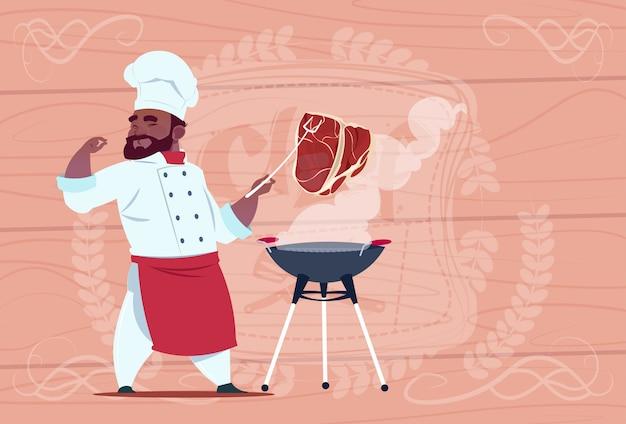 Carne del cuoco unico dell'afroamericano grill meat sul capo del ristorante del fumetto del bbq in uniforme bianca sopra fondo strutturato di legno Vettore Premium