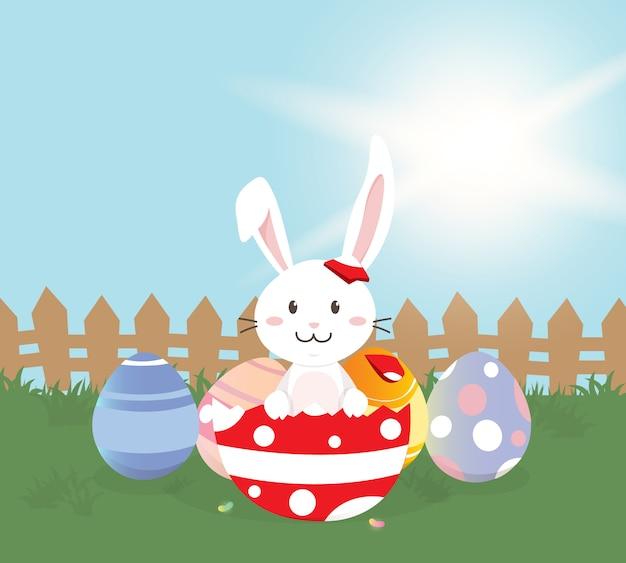 Cartolina d'auguri felice di pasqua, coniglietto sveglio con le uova di pasqua variopinte nel giacimento di primavera. illustrazione vettoriale Vettore Premium