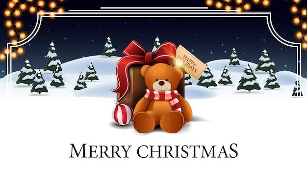 Cartolina di buon natale, bianco e blu con foresta invernale dei cartoni animati con abeti rossi, cielo stellato, ghirlanda e presente con orsacchiotto Vettore Premium