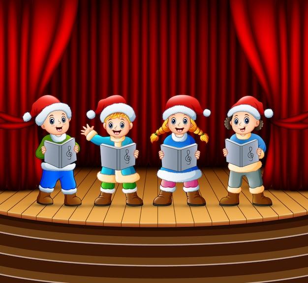 Cartoon bambini cantando canti di natale sul palco Vettore Premium
