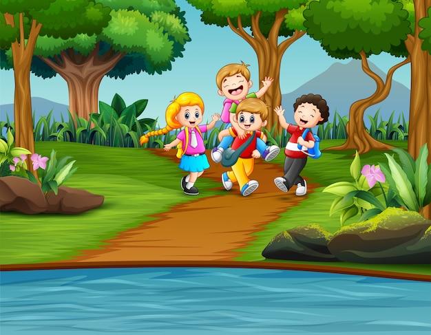 Cartoon bambini che giocano nel parco Vettore Premium