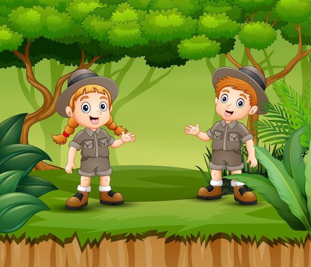 Cartoon boy e girl scout in una foresta Vettore Premium