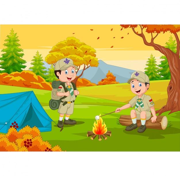 Cartoon scout con tenda e fuoco da campo Vettore Premium