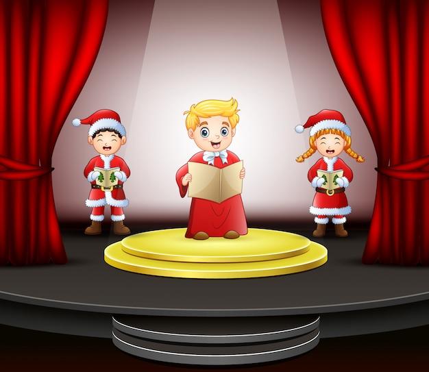 Cartoon tre bambini cantando sul palco Vettore Premium