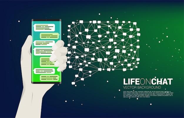 Chatta sul telefono cellulare in mano con il concetto di sfondo discorso bolla poligono per argomento sociale e notizie. Vettore Premium