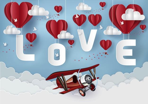 Concetto di san valentino. palloncino rosso che fluttua nel cielo ha la lettera amore ci sono aerei rossi che volano attraverso. stile di arte cartacea Vettore Premium