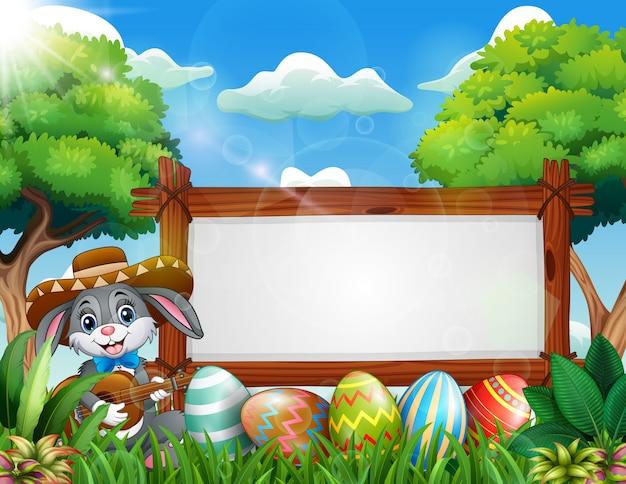 Coniglietto di pasqua che gioca chitarra vicino al segno in bianco e all'uovo di pasqua Vettore Premium