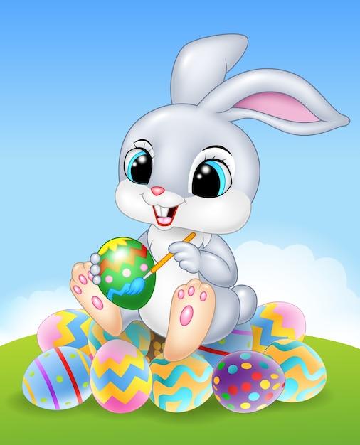 Conigli pasquali seduta su prato circondato da colorate uova di