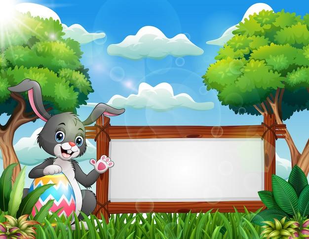 Coniglietto di pasqua in possesso di un grande uovo vicino a un segno in bianco Vettore Premium