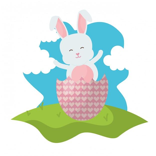 Coniglio carino con uovo di pasqua rotto dipinto nel campo Vettore Premium