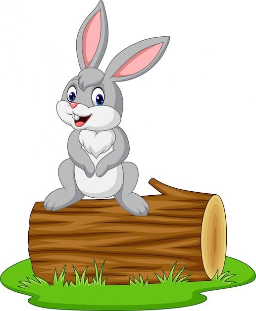 Coniglio cartone animato seduto su un tronco Vettore Premium