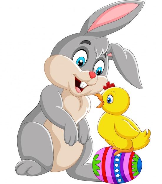 Coniglio del fumetto con un pulcino in piedi sull'uovo di pasqua Vettore Premium