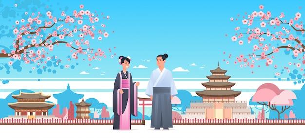 Coppia asiatica che indossa abiti tradizionali uomo donna in costume antico in piedi insieme caratteri cinesi o giapponesi su edifici pagoda paesaggio Vettore Premium