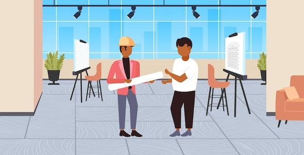 Coppia gli architetti con i modelli acciambellati che discutono il nuovo ingegnere di progetto team il concetto di industria dell'edilizia moderna orizzontale integrale interno dello studio del disegnatore di concetto Vettore Premium