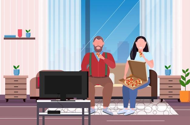 Coppia mangiare la pizza fast food sovrappeso uomo donna guardando la tv seduto sul divano malsano nutrizione obesità concetto moderno salotto interno a figura intera orizzontale Vettore Premium
