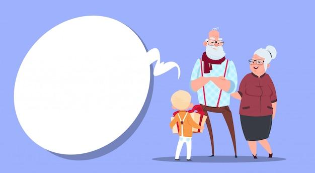 Coppie felici dei nonni con il nipote che dà scatola attuale nonno e nonna e piccolo ragazzo moderni Vettore Premium