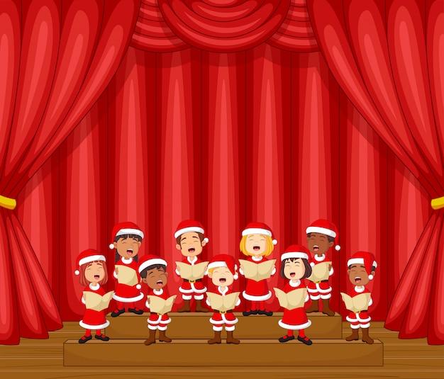 Coro di bambini che cantano una canzone sul palco con il costume di babbo natale Vettore Premium