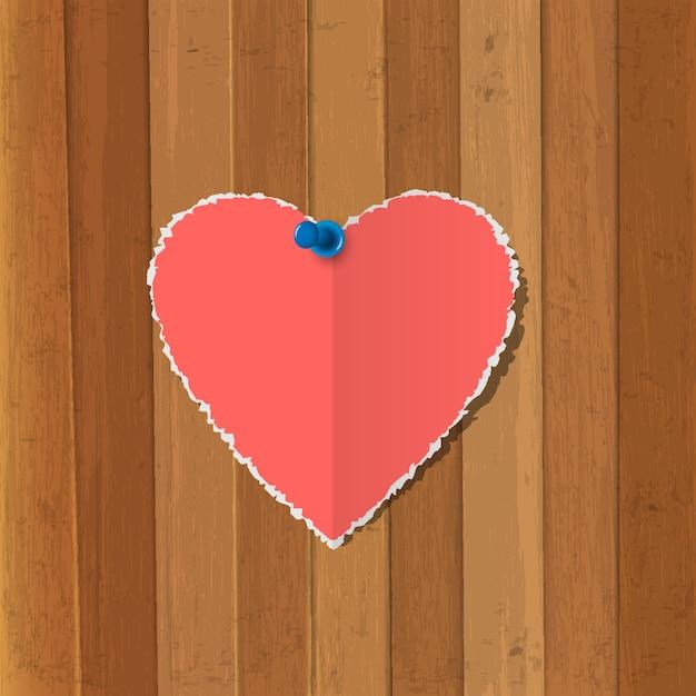 Cuore di carta strappato appuntato su fondo in legno Vettore Premium