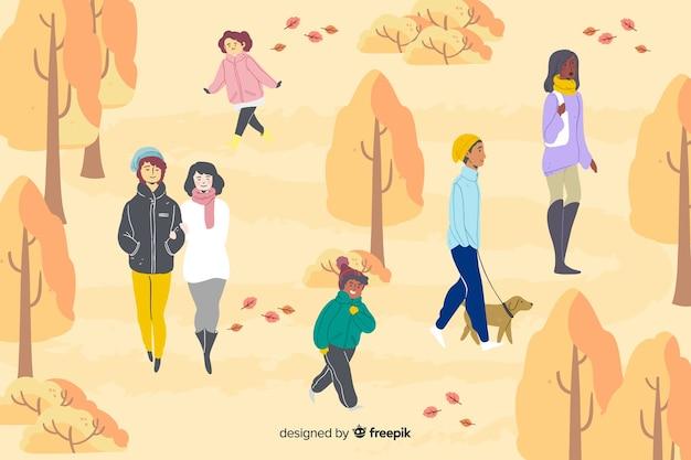 Diverse persone che camminano nel parco in autunno Vettore gratuito