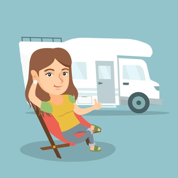 Donna che si siede su una sedia davanti al camper. Vettore Premium