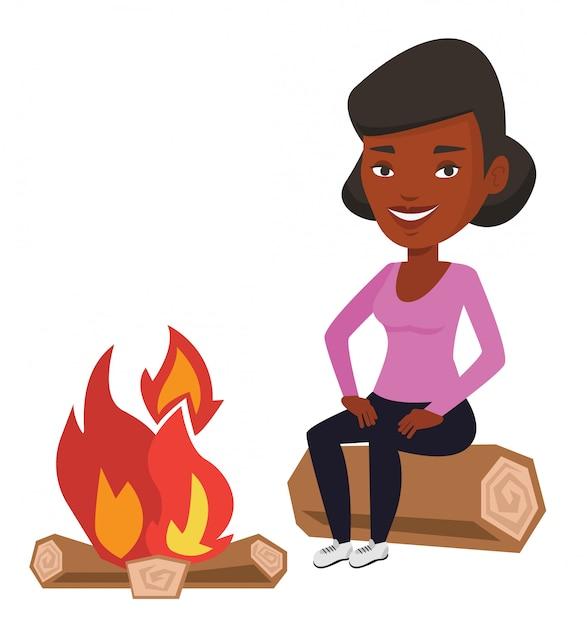 Donna che si siede sul ceppo vicino al fuoco di accampamento nel campeggio. Vettore Premium