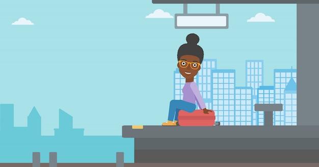 Donna che si siede sulla valigia alla stazione ferroviaria. Vettore Premium