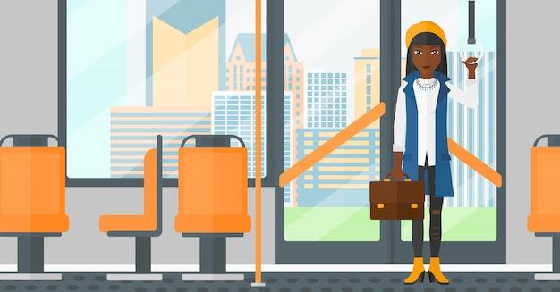 Donna in piedi all'interno del trasporto pubblico. Vettore Premium