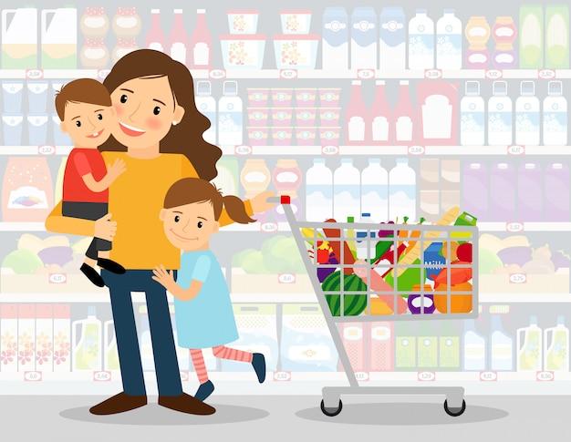 Donna in un supermercato con due bambini piccoli e carrello della spesa pieno di generi alimentari. illustrazione vettoriale Vettore Premium
