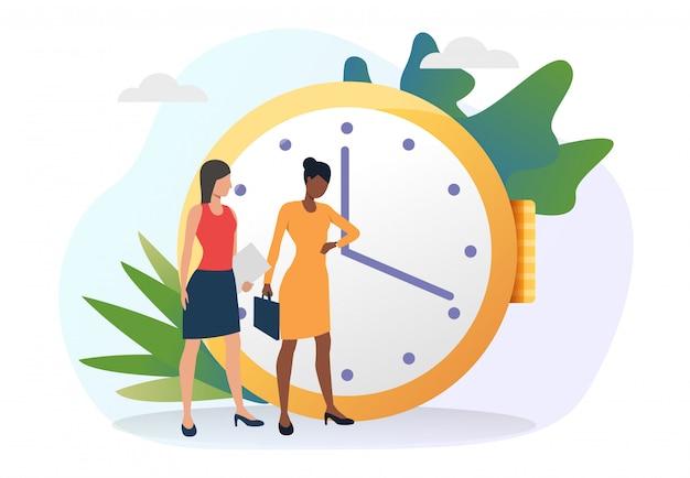 Donne di affari che esaminano le lancette dell'orologio Vettore gratuito