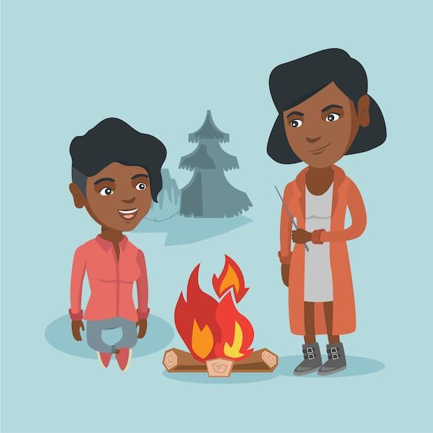 Due amici seduti attorno al falò in campeggio. Vettore Premium
