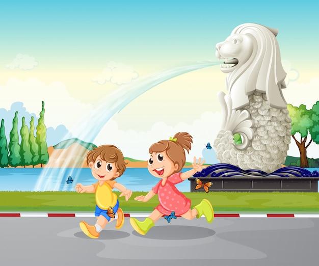 Due bambini che giocano vicino alla statua di merlion Vettore Premium