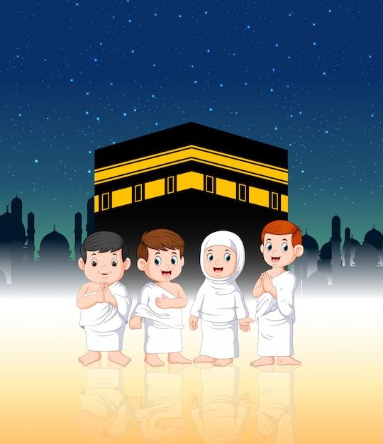 Due bambini con i loro genitori stanno facendo il pellegrinaggio di fronte alla ka'bah Vettore Premium