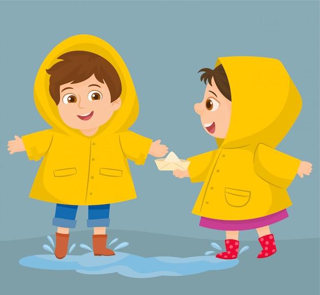 Due bambini divertenti felici sotto la doccia autunnale Vettore Premium