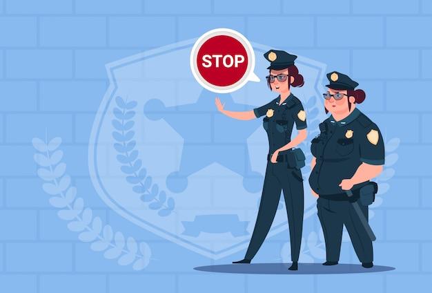 Due donne della polizia che tengono il fanale di arresto che indossa le guardie femminili uniformi sul fondo dei mattoni blu Vettore Premium
