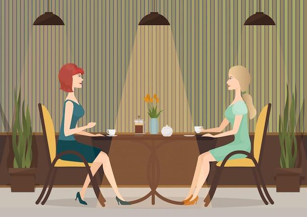 Due giovani donne che bevono caffè nel caffè Vettore Premium