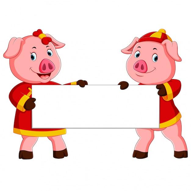 due maiali carini stanno tenendo il bordo bianco per il capodanno cinese Vettore Premium
