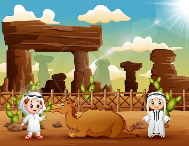 Due ragazzi arabi con i cammelli nel deserto Vettore Premium