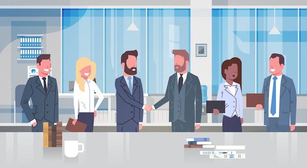 Due uomini d'affari che agitano le mani con gruppi di uomini d'affari in ufficio moderno partner mano scossa con Vettore Premium