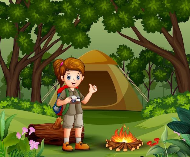 Esploratore di ragazza con uniforme scout campeggio nella foresta Vettore Premium