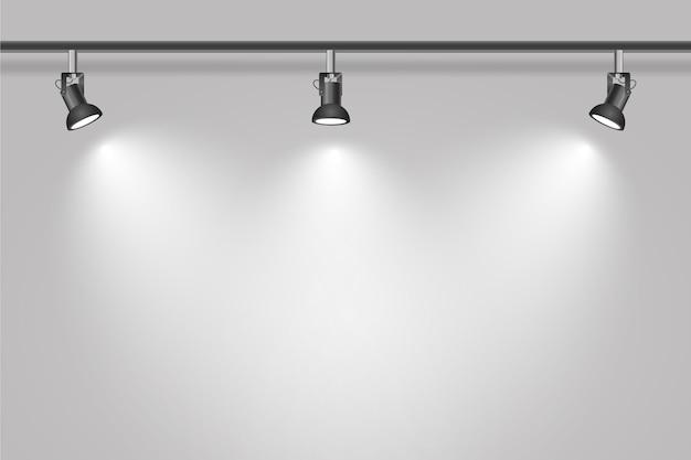 Faretti sul fondo bianco della parete dello studio Vettore gratuito