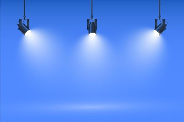 Faretti sul fondo blu della parete dello studio Vettore gratuito