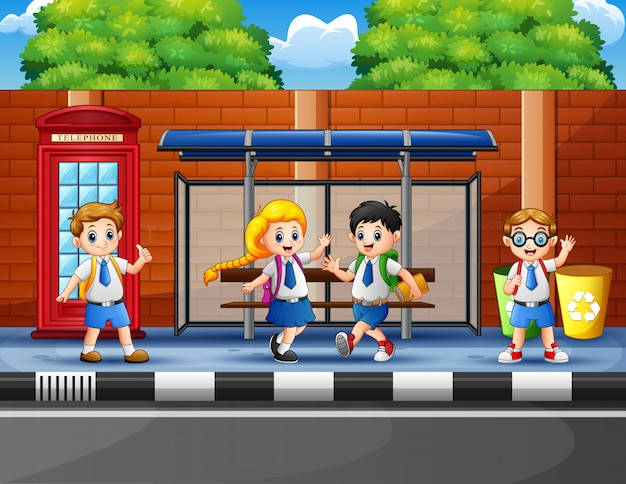 Felici scolari alla fermata dell'autobus Vettore Premium