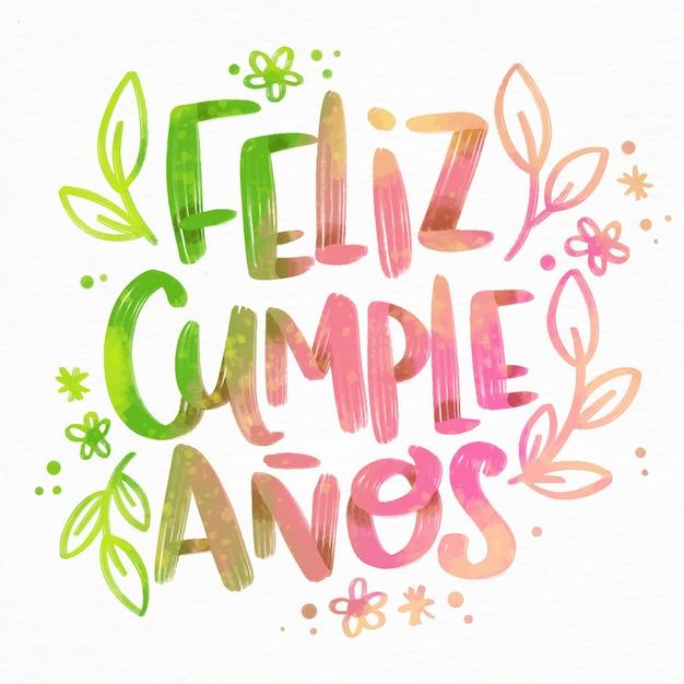 Feliz cumpleaños lettering con fiori e foglie Vettore gratuito