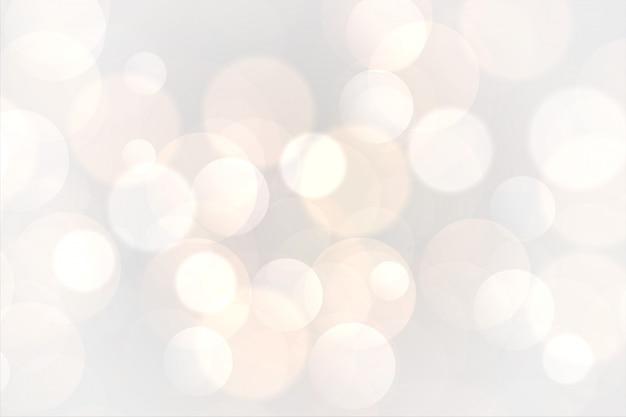 Fondo bianco astratto delle luci d'ardore del bokeh Vettore gratuito