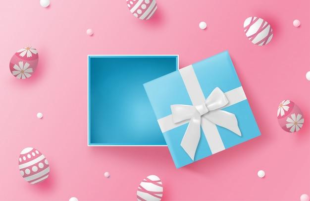 Fondo felice di giorno di pasqua con le uova di pasqua e il contenitore di regalo blu sul rosa Vettore Premium